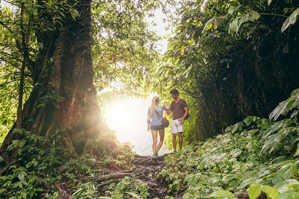 Young man and woman hiking in tropical jungle. Couple of hikers walking along forest trail.